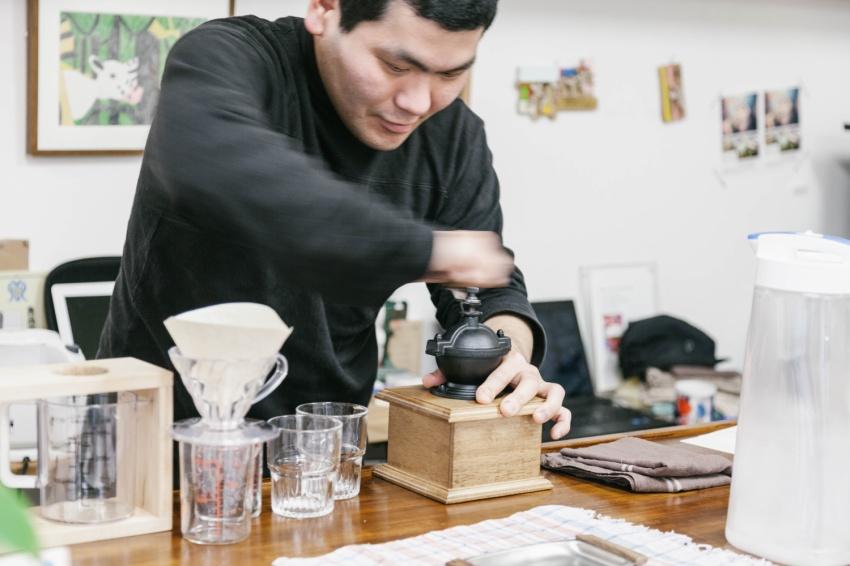 コーヒーを挽く、スタジオクーカの作家・水野 貴男さん。